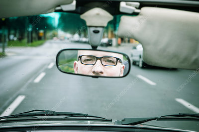 Reflection of young man in rearview mirror