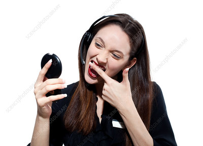 Woman with headset, wiping lipstick off her teeth