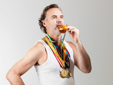 Mature man eating gold coin against white background