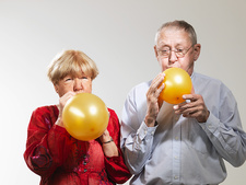 Senior blowing up balloons against white background