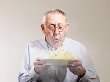 Senior man blowing out candles on birthday cake