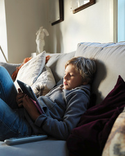 Teenage boy relaxing on sofa and using digital tablet