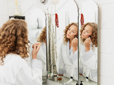 Young woman applying make-up in mirror
