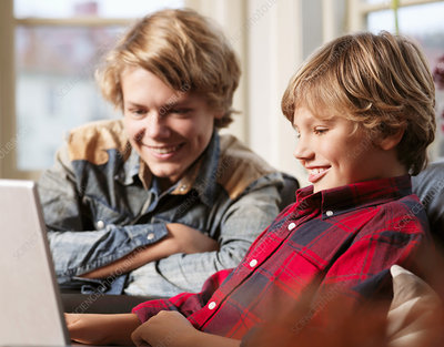 Teenage boy and brother watching laptop
