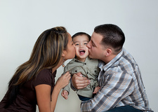 Mother and father kissing toddler son