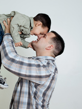 Young man holding son in the air, studio shot