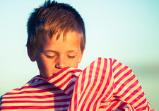 Boy holding striped fabric against face