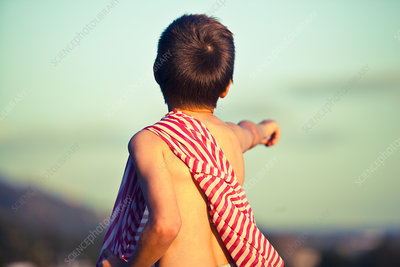 Boy pointing into distance with striped fabric on shoulder