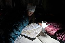 Woman in sleeping bag, looking at trail map, Nepal
