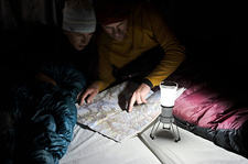 Couple in sleeping bags, looking at trail map, Nepal
