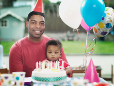 Father and baby boy at birthday party, portrait