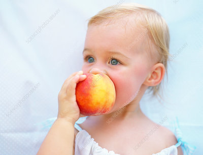 Toddler enjoying peach