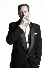 Man wearing a tuxedo and smoking
