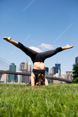 Woman doing headstand with legs apart