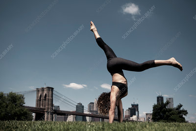Woman doing handstand with legs apart