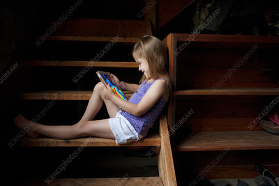Little girl looking at digital tablet