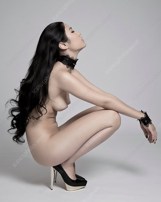 Nude woman crouching in high heels, side view