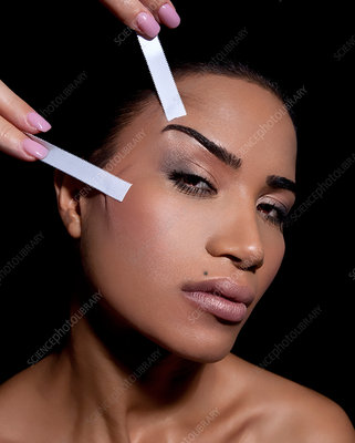 Woman having face lifted with tape