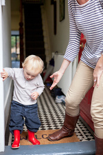 Boy and mother stepping onto doorstep
