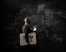 Businessman by blackboard with digital tablet and moodboard