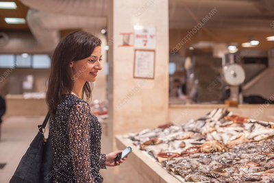 Woman looking at fresh fish in market