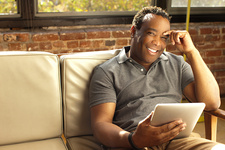 Man posing with charismatic smile holding digital tablet