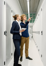 Two employees in discussion in data storage room