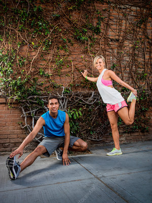Young man and woman stretching before exercise