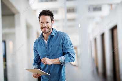 Man with digital tablet looking away