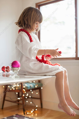 Girl on table playing with Christmas decorations