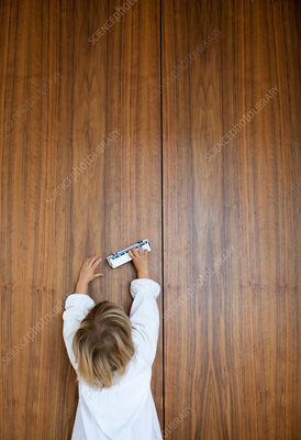 Child playing toy bus on wooden wall