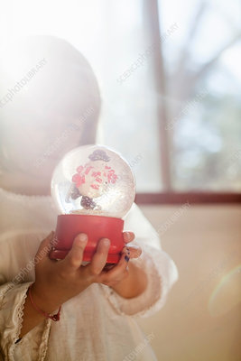 Girl playing with snow globe