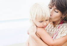 Mother kissing daughter in arms