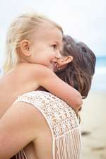 Girl hugging mother tightly around neck