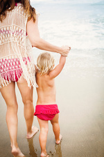 Back view of mother leading child on beach
