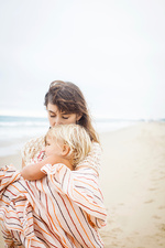 Mother cuddling child wrapped in towel