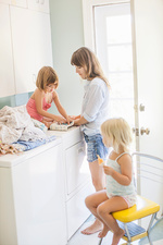 Mother with two daughters folding laundry in utility room
