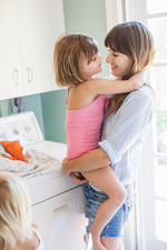 Mother and daughter hugging in utility room, portrait