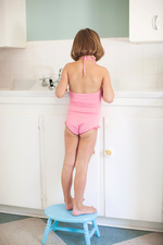 Girl wearing swimsuit standing on stool in bathroom