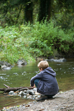 Boy squatting and looking into stream