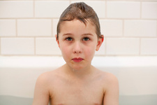 Boy with sad face immersed in bathtub