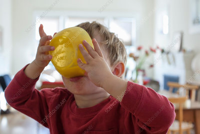 Young boy holding yellow breakfast bowl up to his mouth
