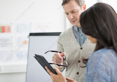 Mature man and mid adult woman using digital tablet