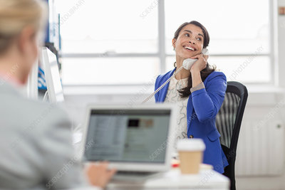 Mid adult businesswoman using telephone in office