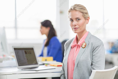 Young businesswoman at desk in office, portrait