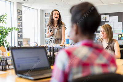 Young woman using telephone in busy creative office