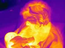 Mature woman breastfeeding newborn son, thermal image