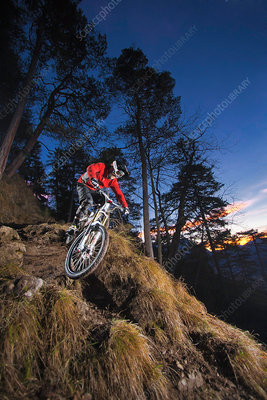 Female mountain biker riding down steep mountain track