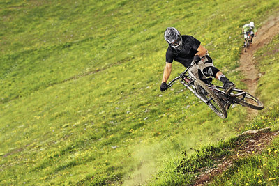 Mountain bikers riding down steep grassy slope