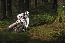 Mountain biker riding muddy forest track
